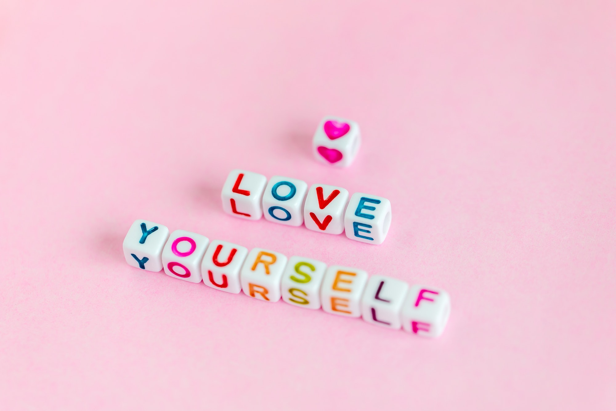 Quote 'Love yourself' on muted pink background